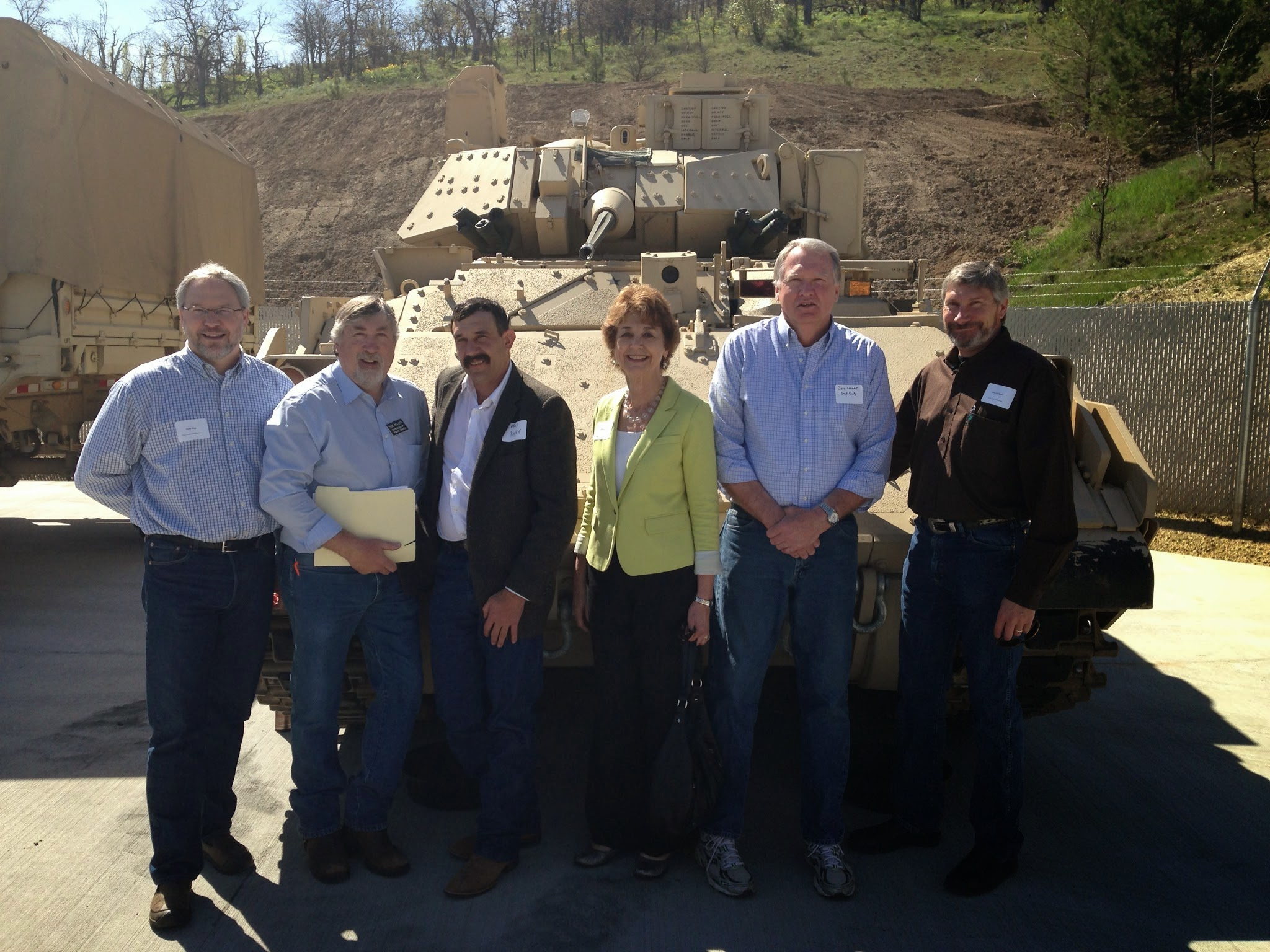 County Commissioners in front of a tank