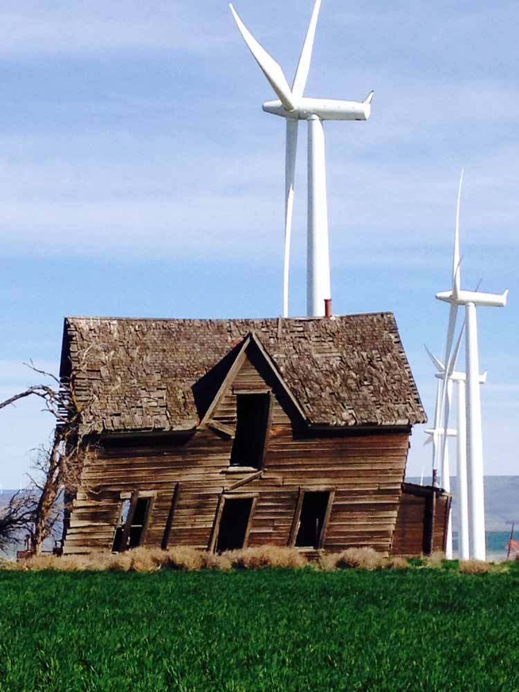Sherman County old building in front of wind turbines