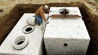 man installing underground septic tanks