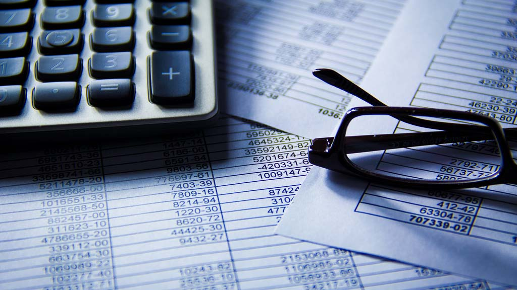 calculator and eyeglasses on financial papers