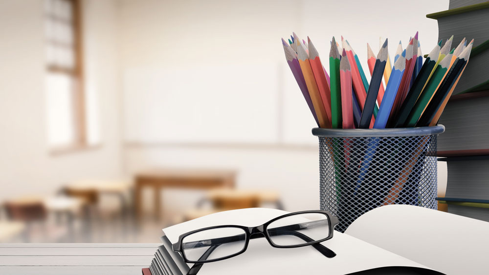 eye glasses resting on a book next to a cup of pencils in the foreground of an empty classroom