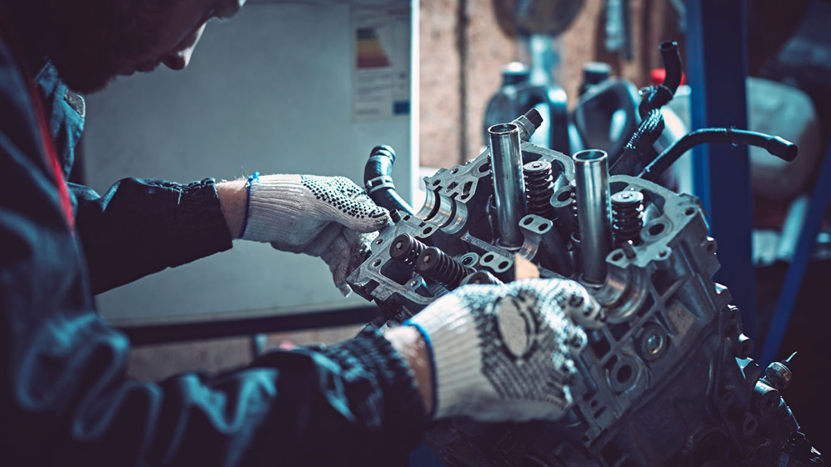 Auto mechanic dismantles the opposing engine.