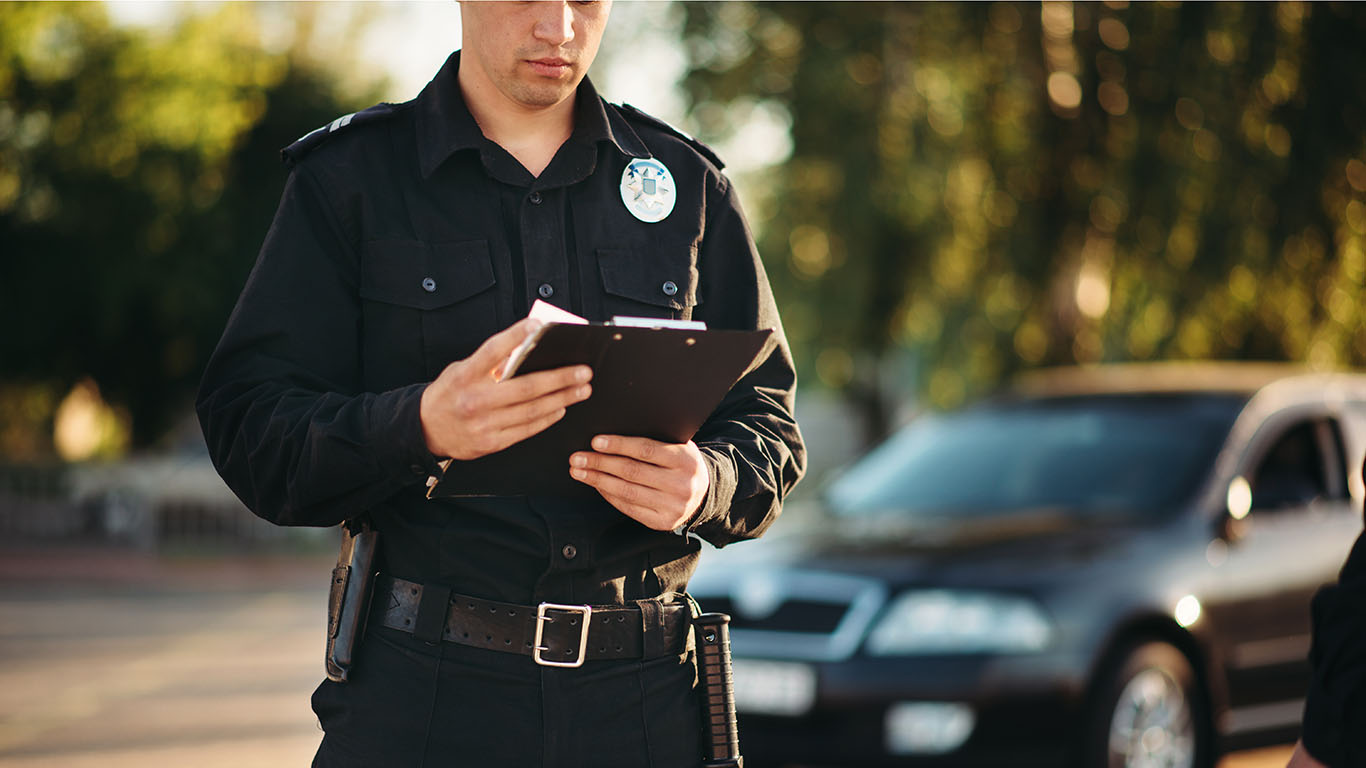 Officer with notebook in hands check the car